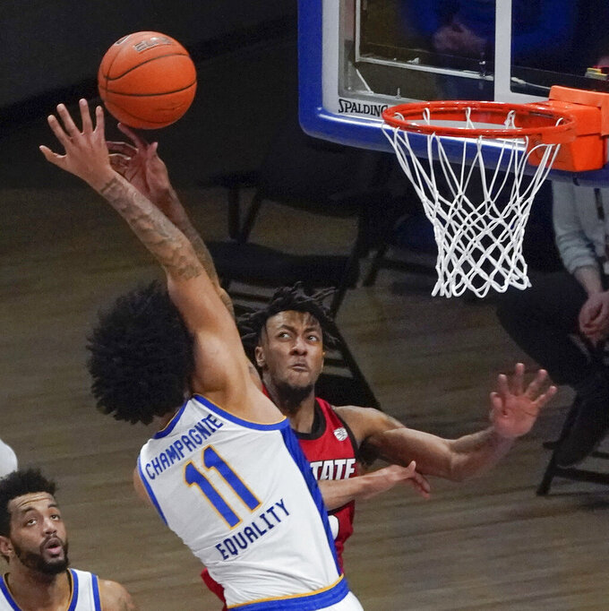Pittsburgh's Justin Champagnie (11) tries a shot as North Carolina State's DJ Funderburk (0) defends with less than 10 seconds left in an NCAA college basketball game Wednesday, Feb. 17, 2021, in Pittsburgh. Champagnie missed and N.C. State won 74-73. (AP Photo/Keith Srakocic)