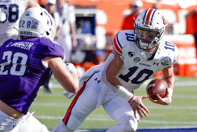 Auburn quarterback Bo Nix (10) scrambles as he is pressured by Northwestern linebacker Chris Bergin (28) during the first half of the Citrus Bowl NCAA college football game, Friday, Jan. 1, 2021, in Orlando, Fla. (AP Photo/John Raoux)