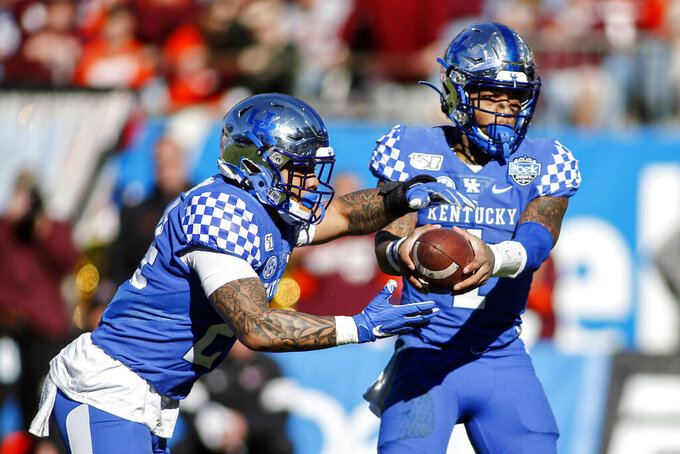 Kentucky quarterback Lynn Bowden Jr. hands off to running back Christopher Rodriguez Jr. who rushes for a touchdown against Virginia Tech in the first half of the Belk Bowl NCAA college football game in Charlotte, N.C., Tuesday, Dec. 31, 2019. (AP Photo/Nell Redmond)