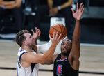 Los Angeles Clippers' Kawhi Leonard (2) fouls Dallas Mavericks' Luka Doncic (77) during the second half of an NBA first round playoff game Sunday, Aug. 30, 2020, in Lake Buena Vista, Fla. (AP Photo/Ashley Landis)
