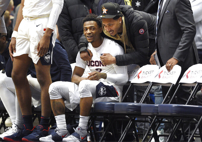 Connecticut's Alterique Gilbert sits and smiles as he is greeted by former teammate NBA G League Erie BayHawks' Jalen Adams before an NCAA college basketball game against Memphis, Sunday, Feb. 16, 2020, in Hartford, Conn. (AP Photo/Jessica Hill)