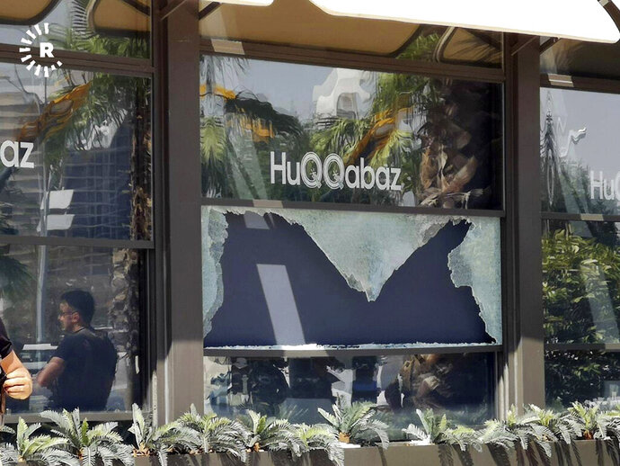 This image posted by RUDAW Facebook TV, an Irbil-based Kurdish broadcaster, shows  broken glass shows in the window of a restaurant that was the scene of a shooting, in Irbil, Iraq, Wednesday, July 17, 2019. Turkey's state-run news agency says a Turkish diplomat working at Ankara's consulate in the northern Iraqi city of Irbil was killed during a shooting attack inside the restaurant there. (RUDAW Facebook TV via AP)