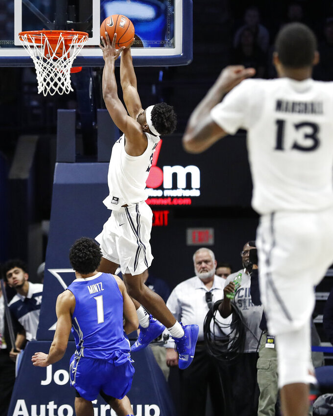 Xavier's Quentin Goodin (3) scores against Creighton's Davion Mintz (1) to tie the score during the second half of an NCAA college basketball game Wednesday, Feb. 13, 2019, in Cincinnati. (AP Photo/John Minchillo)