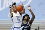 North Carolina forward Armando Bacot (5) and Duke guard DJ Steward reach for a rebound during the second half of an NCAA college basketball game in Chapel Hill, N.C., Saturday, March 6, 2021. (AP Photo/Gerry Broome)