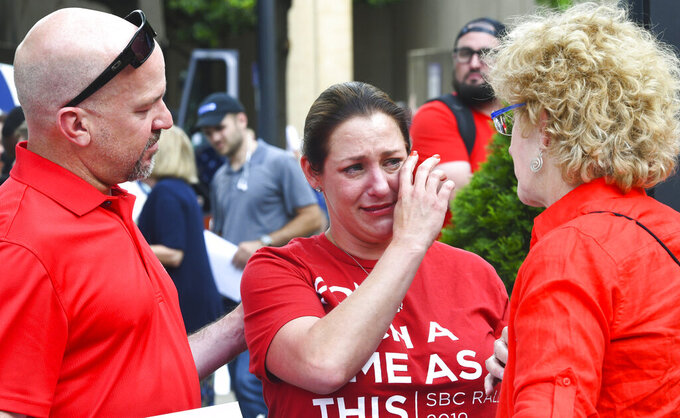 FILE - In this Tuesday, June 11, 2019 file photo, Jules Woodson, center, of Colorado Springs, Colo., is comforted by her boyfriend Ben Smith, left, and Christa Brown while demonstrating outside the Southern Baptist Convention's annual meeting in Birmingham, Ala. First-time attendee Woodson spoke through tears as she described being abused sexually by a Southern Baptist minister. (AP Photo/Julie Bennett, File)
