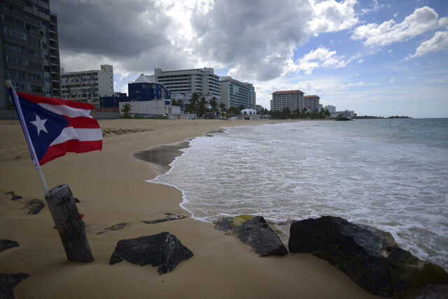 FILE - In this May 21, 2020 file photo, a Puerto Rican flag flies on an empty beach at Ocean Park, in San Juan, Puerto Rico. Puerto Rico's governor announced Thursday, June 11, that she will lift nearly all restrictions aimed at curbing coronavirus cases, which means beaches, churches and businesses including movie theaters and gyms across the U.S. territory will reopen after three months. (AP Photo/Carlos Giusti, File) PUERTO RICO OUT-NO PUBLICAR EN PUERTO RICO