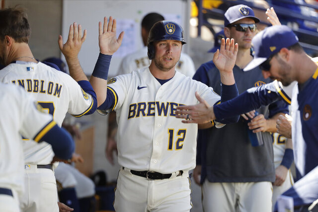 FILE - In this March 1, 2020, file photo, Milwaukee Brewers' Justin Smoak is congratulated after scoring during a spring training baseball game against the Cincinnati Reds in Phoenix. The Brewers added first baseman/designated hitter Daniel Vogelbach and designated Smoak for assignment as they attempt to boost their struggling lineup and make another September surge. (AP Photo/Darron Cummings, File)