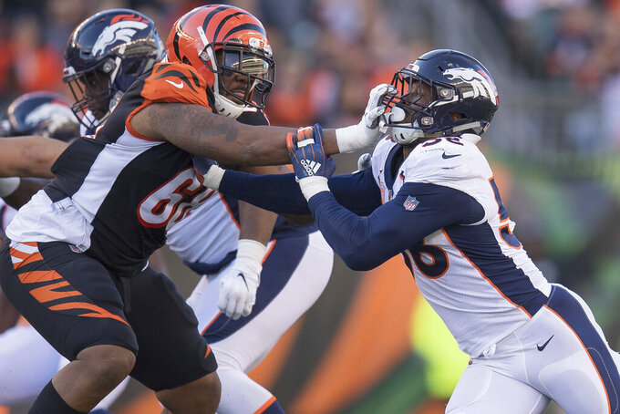 FILE - In this Dec. 2, 2018, file photo, Cincinnati Bengals offensive tackle Bobby Hart (68) grabs the face mask of Denver Broncos outside linebacker Von Miller (58) during the second half of the NFL football game played in Cincinnati. The Bengals are keeping right Hart with a three-year deal.  The Bengals signed Hart as a free agent from the Giants last year as a stopgap measure, trying to improve their horrid line. Hart started all 16 games, but the right side of the line struggled as Cincinnati finished with a third straight losing season.   (AP Photo/Bryan Woolston, File)