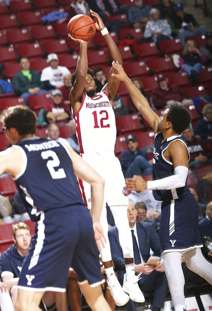 Massachusetts' Carl Pierre (12) launches up a 3-pointer from the corner over Yale's Azar Swian (5) during an NCAA college basketball game, Wednesday, Dec. 11, 2019 in Amherst, Mass. ( J. Anthony Roberts/The Republican via AP)