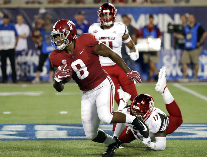 Alabama running back Josh Jacobs (8) gains yardage as he slips away from Louisville linebacker Dorian Etheridge (17) during the first half of an NCAA college football game Saturday, Sept. 1, 2018, in Orlando, Fla. (AP Photo/John Raoux)