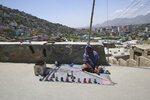 A woman cobbler waits for customers in Kabul, Afghanistan, Monday, May 18, 2020. (AP Photo/Rahmat Gul)
