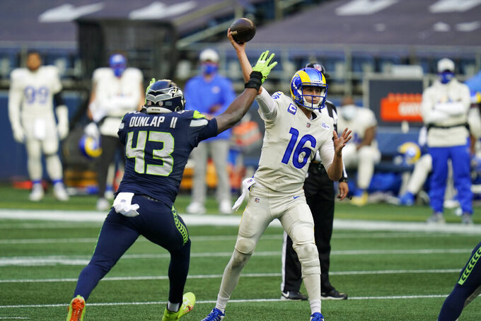 Los Angeles Rams quarterback Jared Goff (16) passes under pressure from Seattle Seahawks defensive end Carlos Dunlap II (43) during the first half of an NFL football game, Sunday, Dec. 27, 2020, in Seattle. (AP Photo/Elaine Thompson)