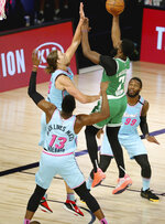 Boston Celtics guard Jaylen Brown (7) shoots against Miami Heat forward Kelly Olynyk (9) and forward Bam Adebayo (13) and forward Jae Crowder (99) during the second half of an NBA basketball game Tuesday, Aug. 4, 2020, in Lake Buena Vista, Fla. (Kim Klement/Pool Photo via AP)