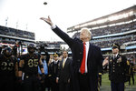 FILE - In this Dec. 8, 2018, file photo, President Donald Trump tosses the coin before the Army-Navy NCAA college football game in Philadelphia. The 120th Army-Navy game is set for Saturday in Philadelphia.  President Donald Trump will attend his second straight Army-Navy game. Presidents, by custom, sit on the Army side of the stadium for one half and the Navy side for the other. (AP Photo/Matt Rourke, File)