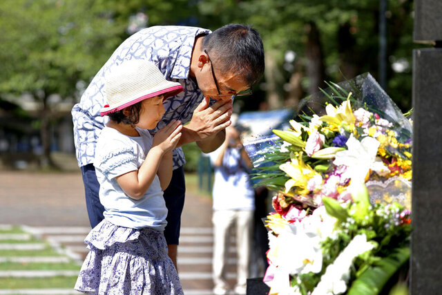 A man and his daughter pray for the victims of U.S. atomic bombing at the Atomic Bomb Hypocenter Park in Nagasaki, southern Japan, Sunday, Aug. 9, 2020. Nagasaki marked the 75th anniversary of the atomic bombing on Sunday. (Takuto Kaneko/Kyodo News via AP)