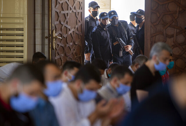 Palestinian Hamas police stand guard at the entrance of a mosque as worshipers attend the last Friday noon Prayer of the holy month of Ramadan, in Gaza City, Friday, May. 22, 2020. After nearly two months of closure due to the coronavirus, Gaza's Hamas rulers decided to partially reopen mosques for the Friday noon prayer.  (AP Photo/Khalil Hamra)