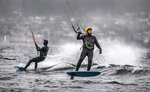 In this Monday, Jan. 6, 2020, photo, Jim Buttrick of Seattle was out in the wind (24-33 mph) and the rain with friends off Magnuson Park riding a hydrofoil kiteboard lifting him above the waves. He described it,