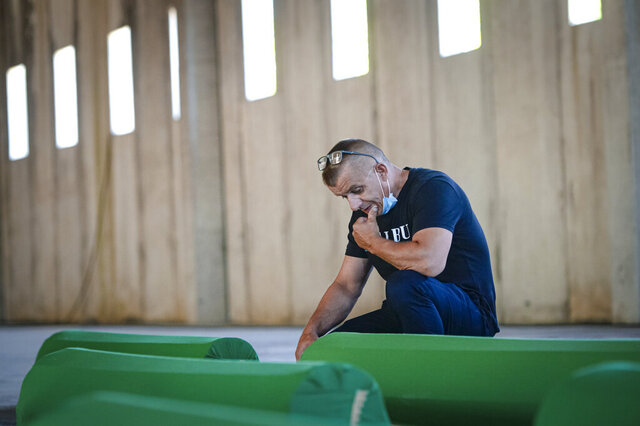 Survivor Bahrudin Salihovic sits by the coffin of his father, inside the former UN base in Potocari, near Srebrenica, Bosnia, Friday, July 10, 2020. Nine newly found and identified men and boys will be laid to rest when Bosnians commemorate on Saturday 25 years since more than 8,000 Bosnian Muslims perished in 10 days of slaughter, after Srebrenica was overrun by Bosnian Serb forces during the closing months of the country's 1992-95 fratricidal war, in Europe's worst post-WWII massacre. (AP Photo/Kemal Softic)