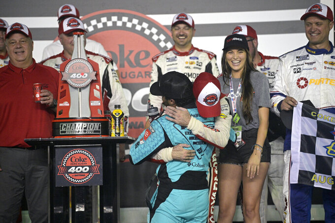 Ryan Blaney receives a hug from Bubba Wallace, front, in Victory Lane after winning a NASCAR Cup Series auto race at Daytona International Speedway, Saturday, Aug. 28, 2021, in Daytona Beach, Fla. (AP Photo/Phelan M. Ebenhack)