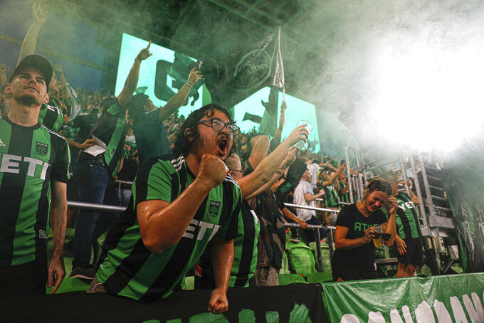 Austin FC fans celebrate by throwing water and beer in the air after the team scored its third goal against the Portland Timbers during an MLS soccer match Saturday, Aug. 21, 2021, in Austin, Texas. (Aaron E. Martinez/Austin American-Statesman via AP)