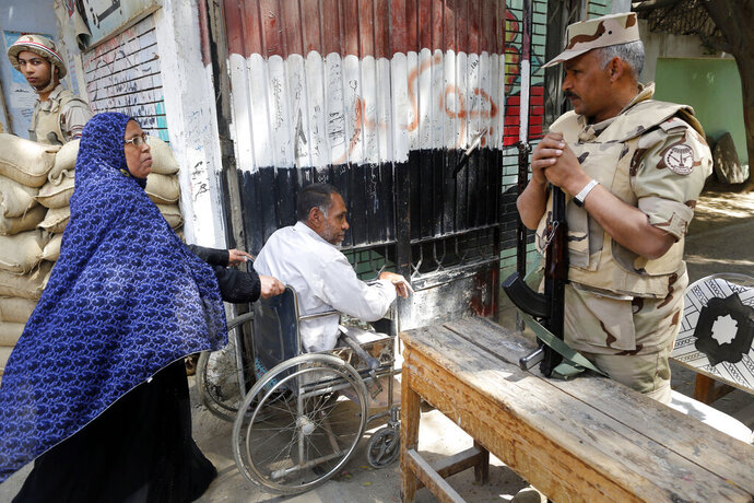 Army officers secure a polling station as people enter to vote on constitutional amendments on the second day of a nationwide referendum in Cairo, Egypt, Sunday April 21, 2019. Egyptians are voting on constitutional amendments that would allow el-Sissi to stay in power until 2030. (AP Photo/Amr Nabil)