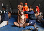 In this Jan. 27, 2019, photo, Hindu men get their hair cut in a ritual before becoming Naga Sadhus or naked holy men at Sangam, the confluence of three holy rivers during the Kumbh Mela or pitcher festival in Prayagraj Uttar Pradesh state, India. At every Kumbh, including this year's, thousands of devotees were initiated into the reclusive sect of the Naga Sadhus, naked, ash-smeared cannabis-smoking Hindu warriors and onetime-armed defenders of the faith who for centuries have lived as ascetics in jungles and caves. (AP Photo/ Rajesh Kumar Singh)