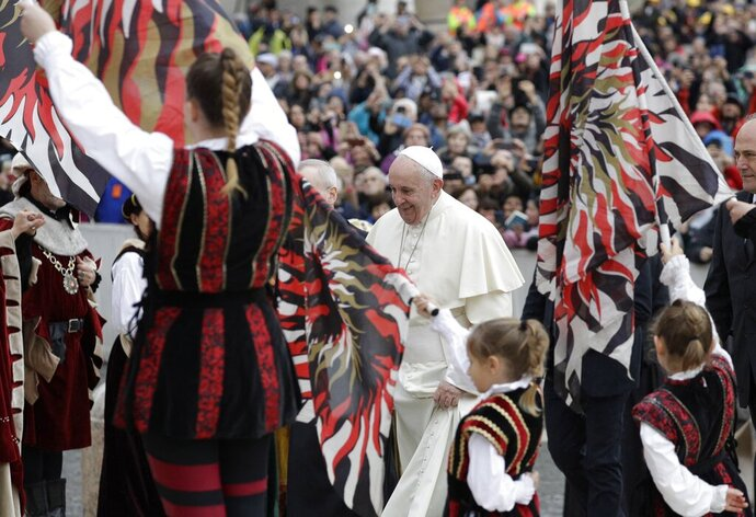 Pope Francis walks through a group of flag bearers as he arrives for his weekly general audience in St. Peter's Square, at the Vatican, Wednesday, Nov. 13, 2019. (AP Photo/Gregorio Borgia)
