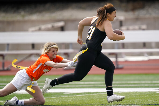 Ottawa quarterback Madysen Carrera (21) is tackled by Midland defender Casey Thompson, left, during an NAIA flag football game in Ottawa, Kan., Friday, March 26, 2021. The National Association of Intercollegiate Athletics introduced women's flag football as an emerging sport this spring. (AP Photo/Orlin Wagner)