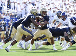 Navy quarterback Malcolm Perry hands off to Nelson Smith in the second quarter of an NCAA college football game against Holy Cross, Saturday, Aug. 31, 2019, in Annapolis, Md. (Paul W. Gillespie/Capital Gazette via AP)