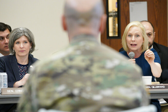 Sen. Kirsten Gillibrand, D-N.Y., right, directs a question to Maj. Gen. Scott Spellmon, deputy commanding general, civil and emergency operations of the U.S. Army Corps of Engineers, center, as Sen. Joni Ernst, R-Iowa, left, listens, during a field hearing of the Senate Committee on Environment and Public Works, in Glenwood, Iowa, Wednesday, April 17, 2019. The hearing was called to investigate the U.S. Army Corps of Engineers' Management of the 2019 Missouri River Basin Flooding. (AP Photo/Nati Harnik)
