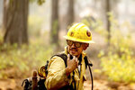 A firefighter mops up hot spots in the Trail of 100 Giants grove of Sequoia National Forest, Calif., on Monday, Sept. 20, 2021. (AP Photo/Noah Berger)