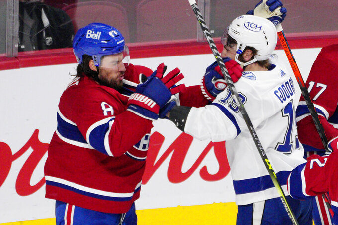 Montreal Canadiens defenseman Ben Chiarot (8) and Tampa Bay Lightning right wing Barclay Goodrow (19) throw punches after a stop in play during the third period of Game 4 of the NHL hockey Stanley Cup final in Montreal, Monday, July 5, 2021. (Paul Chiasson/The Canadian Press via AP)