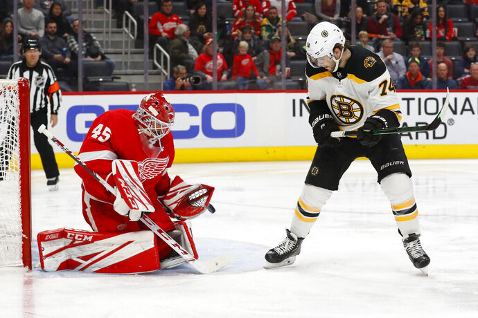 Detroit Red Wings goaltender Jonathan Bernier (45) stops a shot as Boston Bruins left wing Jake DeBrusk (74) waits for the rebound in the third period of an NHL hockey game Sunday, Feb. 9, 2020, in Detroit. (AP Photo/Paul Sancya)