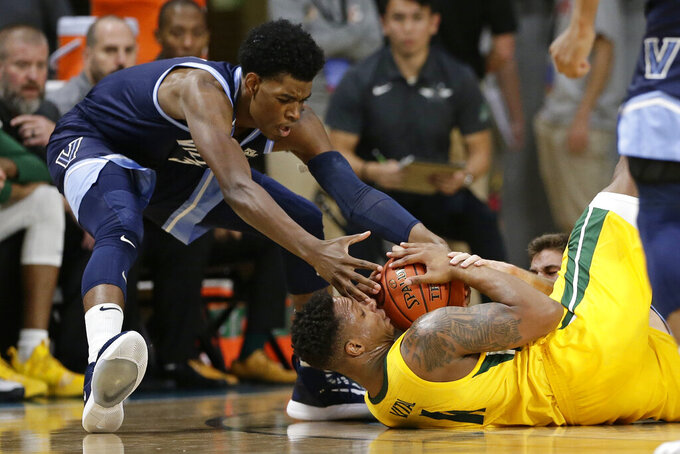 Villanova forward Brandon Slater reaches for the ball while Baylor guard Mark Vital (11) falls to the floor during the first half of an NCAA college basketball championship game at the Myrtle Beach Invitational in Conway, S.C., Sunday, Nov. 24, 2019. (AP Photo/Gerry Broome)