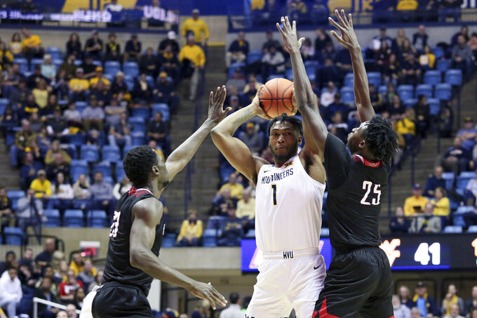 West Virginia forward Derek Culver (1) is defended by Nicholls State forward Elvis Harvey Jr. (23) and forward Warith Alatishe (25) as he goes to pass the ball during the second half of an NCAA college basketball game Saturday, Dec. 14, 2019, in Morgantown, W.Va. Culver had 16 points against Nicholls State. (AP Photo/Kathleen Batten)