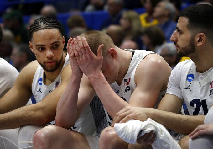 Marquette's Joey Hauser, middle, covers his face as teammates Theo John, left, and Joseph Chartouny, right, sit next to him during the second half of a first-round game against Murray State in the NCAA men's college basketball tournament Thursday, March 21, 2019, in Hartford, Conn. Murray State won 83-64. (AP Photo/Elise Amendola)