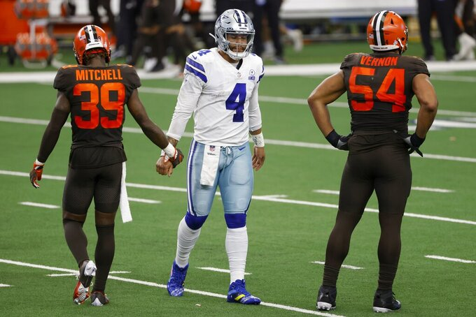 Cleveland Browns cornerback Terrance Mitchell (39) bumps hands with Dallas Cowboys quarterback Dak Prescott (4) after Prescott threw an interception late in the second half of an NFL football game in Arlington, Texas, Sunday, Oct. 4, 2020. The Browns' Olivier Vernon (54) stands nearby after the play. (AP Photo/Ron Jenkins)