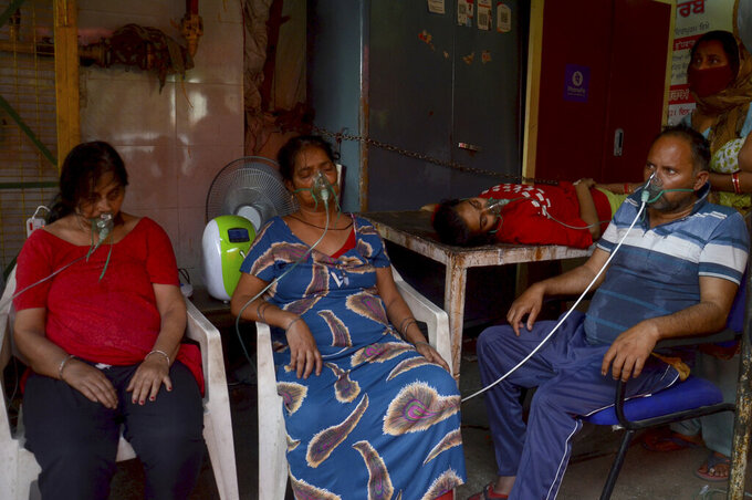 FILE - In this May 1, 2021, file photo, COVID-19 patients receive oxygen outside a Gurdwara, a Sikh house of worship, in New Delhi, India. COVID-19 infections and deaths are mounting with alarming speed in India with no end in sight to the crisis. People are dying because of shortages of bottled oxygen and hospital beds or because they couldn't get a COVID-19 test. (AP Photo/Amit Sharma, File)