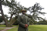 Terry E. Brown, Superintendent of the Fort Monroe National Monument stands in front of what he calls the witness tree, a 500-year-old oak, that was near the the spot of the first landing of Africans in America 400 years ago at Fort Monroe in Hampton, Va., Thursday, Aug. 15, 2019. (AP Photo/Steve Helber)