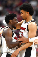 Louisville guard Darius Perry (2), left, and forward Jordan Nwora (33) celebrate a play during the second half of an NCAA college basketball game against Akron in Louisville, Ky., Sunday, Nov. 24, 2019. (AP Photo/Timothy D. Easley)