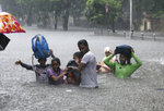 FILE - In this Sept. 4, 2019, file photo, people hold hands and navigate their way through a flooded street as it rains in Mumbai, India. The number of people threatened by climate change-triggered flooding is about three times higher than previously thought, a new study says. But it's not because of more water. It's because the land, especially in Asia and the developing world, is several feet lower than what space-based radar has calculated, according to a study in the journal Nature Communications Tuesday, Oct. 29. (AP Photo/Rajanish Kakade, File)