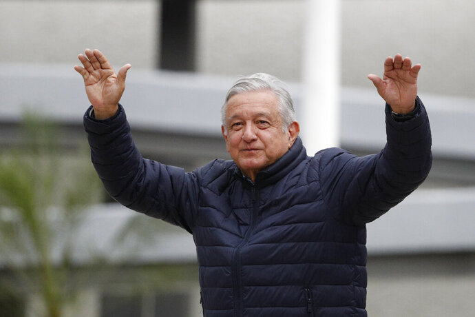 FILE - In this April 3, 2020 file photo, Mexican President Andres Manuel Lopez Obrador waves to supporters cheering from over an outside wall, after visiting a Mexican Social Security Institute (IMSS) hospital that will be converted to receive COVID-19 patients in the Coyoacan district of Mexico City. (AP Photo/Rebecca Blackwell, File)