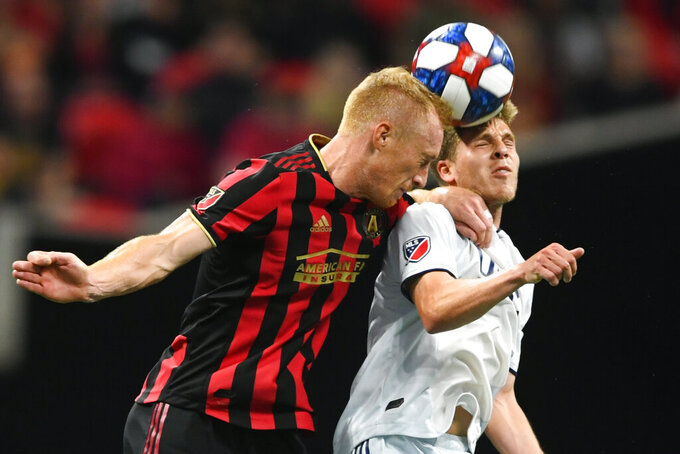 "FILE - In this Oct. 19, 2019, file photo, Atlanta United defender Jeff Larentowicz, left, and New England Revolution midfielder Scott Caldwell battle for a header during round one of an MLS Cup playoff soccer game in Atlanta. Atlanta United veteran defender Jeff Larentowicz, who serves as an executive board member for the players union, said Thursday, June 4, 2020, he has safety concerns about an agreement announced Wednesday for a MLS tournament in Orlando in July. He is worried about the ongoing coronavirus pandemic and said ""We play a contact sport and the virus is a serious thing that puts us all in danger."" (AP Photo/John Amis, File)"