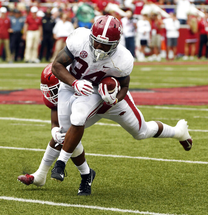 Alabama running back Damien Harris is tackled by Arkansas defender Dre Greenlaw in the second half of an NCAA college football game Saturday, Oct. 6, 2018, in Fayetteville, Ark. (AP Photo/Michael Woods)