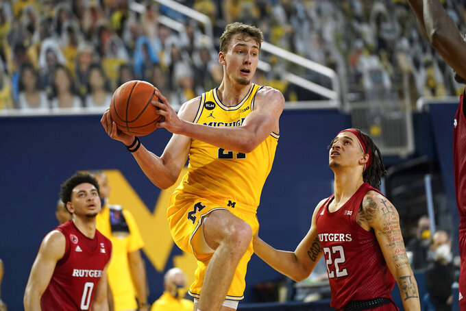 Michigan Wolverines guard Franz Wagner (21) drives on Rutgers guard Caleb McConnell (22) in the second half of an NCAA college basketball game in Ann Arbor, Mich., Thursday, Feb. 18, 2021. (AP Photo/Paul Sancya)