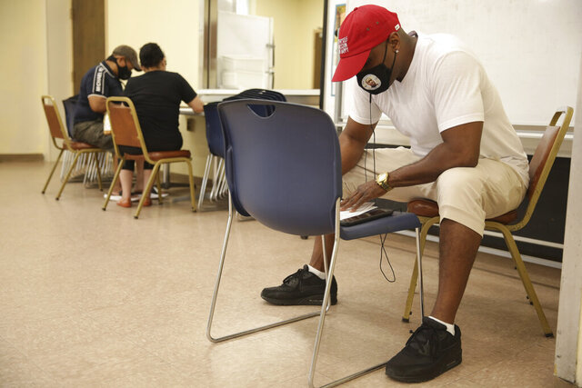 Ajaye' Brewington fills out a provisional ballot at a polling site in Hackensack, N.J., Tuesday, July 7, 2020. Voters have until 8 p.m. to have their ballot postmarked or dropped at one of at least five boxes per county. Half of the polling places in each county must also stay open for voters to cast a ballot in person, though that means they must use a provisional ballot that will be counted once officials determine one has not been mailed to county election officials already. (AP Photo/Seth Wenig)