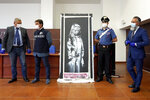 Italian authorities unveil a stolen artwork painted by the British artist Banksy as a tribute to the victims of the 2015 terror attacks at the Bataclan music hall in Paris,  during a press conference in L' Aquila, Italy, Thursday June, 11, 2020 . The L'Aquila prosecutors office said the work was recovered on Wednesday during a search of a home in Tortoreto, a city near the Adriatic coast in the Abruzzo region's Teramo province.  (AP Photo/Andrea Rosa)