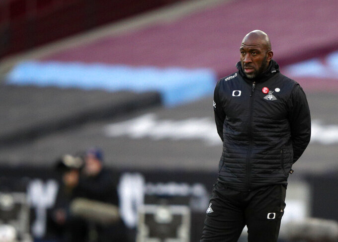 FILE - In this Saturday, Jan. 23, 2021 file photo, Darren Moore looks on during the English FA Cup fourth round soccer match between West Ham United and Doncaster Rovers at the London Stadium in London. Sheffield Wednesday manager Darren Moore says he has developed pneumonia and blood clots on his lungs following a recent coronavirus infection. The 46-year-old Moore returned from the requisite COVID-19 isolation period on Monday, April 12 but felt discomfort the next night following the Owls' 2-0 loss to Swansea. (AP Photo/Ian Walton, file)