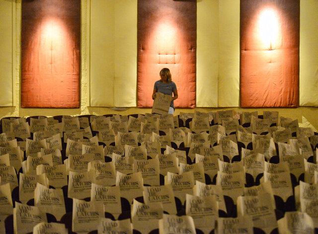 Natalie Knowles, afternoon talent at Bratt FM, puts a paper bag with food donations into a seat inside the Latchis Theatre in Brattleboro, Vt., during the 11th annual Load the Latchis event on Thursday, Aug. 27, 2020. (Kristopher Radder/The Brattleboro Reformer via AP)