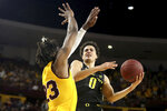 Oregon's Will Richardson (0) drive to the basket against Arizona State's Romello White (23) during the first half of an NCAA college basketball game Thursday, Feb. 20, 2020, in Tempe, Ariz. (AP Photo/Darryl Webb)